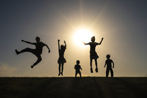 silhouettes of kids jumping