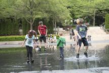 kids splashing in a puddle