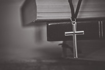 cross necklace hanging from a stack of Bibles