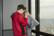 boy looking down at a city through a viewfinder scope