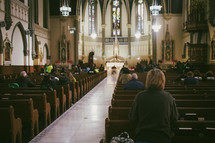 A woman praying during mass at a Catholic church