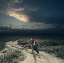 man carrying a cross along a dirt road