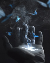 glowing butterflies and smoke from a hand