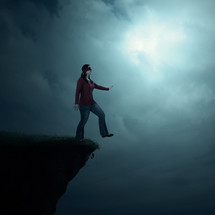 A blindfolded woman walking off the edge of a cliff.