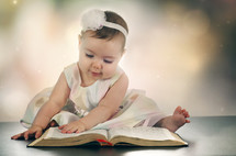 an infant turning the pages of a Bible