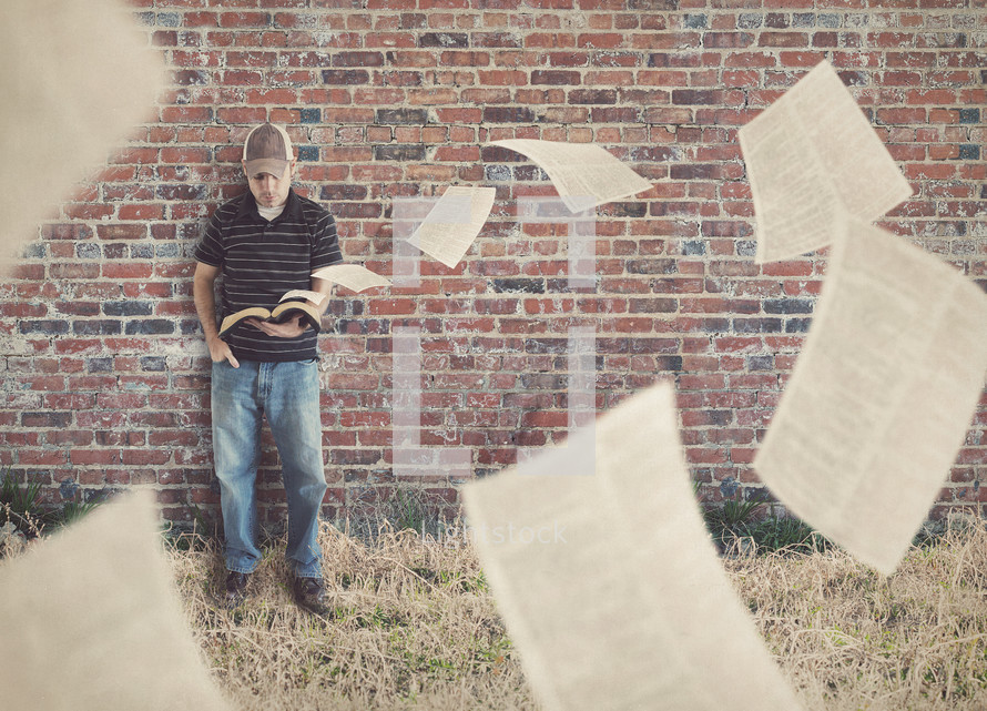 man reading a Bible as pages are being blown away