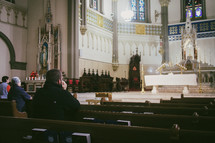 A young Catholic man praying at Eucharistic adoration in a Catholic church