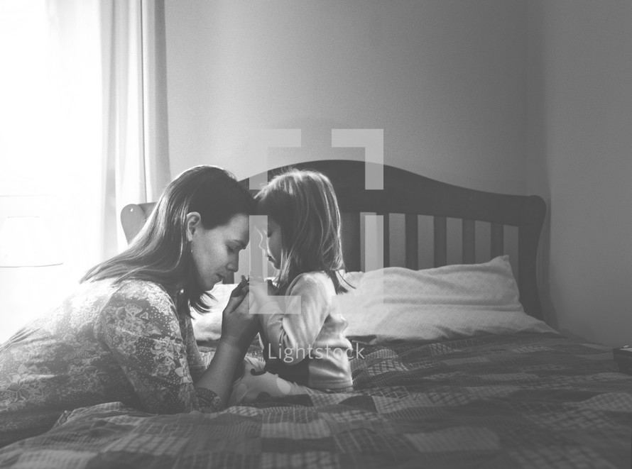 A mother and daughter in prayer at bedtime