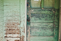 Porch of home with rustic door and weathered green paint.