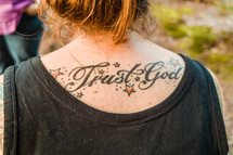 Tattoo on a woman's back - trust in God