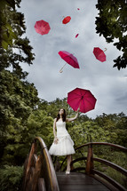 A woman standing on a bridge with umbrella- sky full of umbrellas