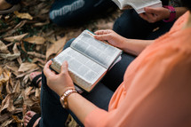 group reading a Bible over fall leaves on the ground