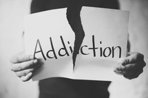 tearing apart a piece of paper with the word addiction on it