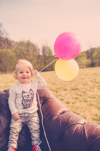 toddler boy holding balloons