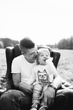 father and daughter sitting in a chair outdoors