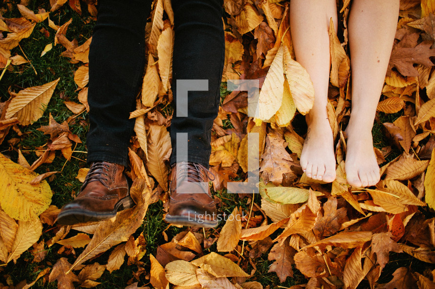 feet of a couple lying in a pile of leaves
