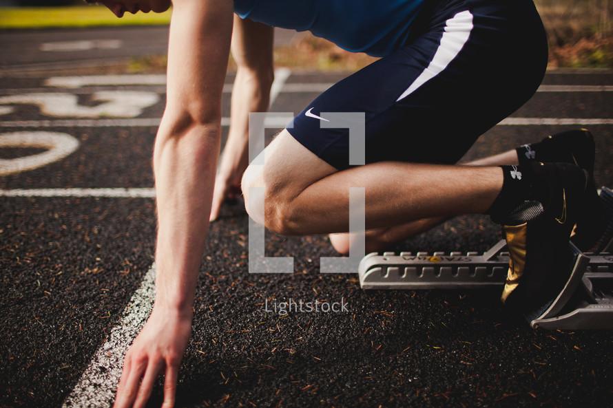 Track runner in sprint position