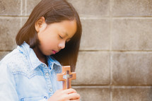 girl holding a wooden cross