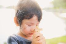 toddler girl holding a wooden cross