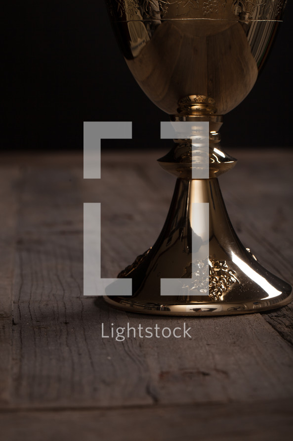 A golden communion goblet on a rustic wooden table.