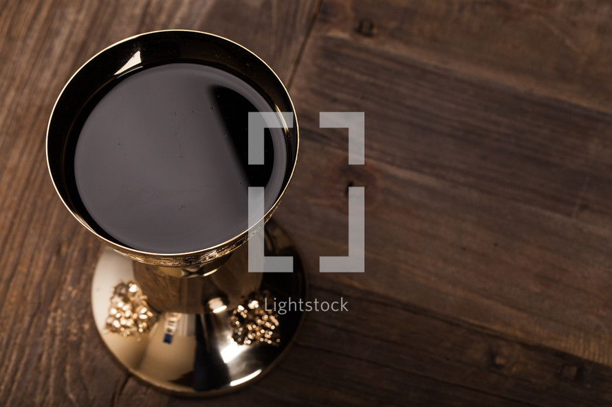 A golden goblet full of wine on a wooden surface.