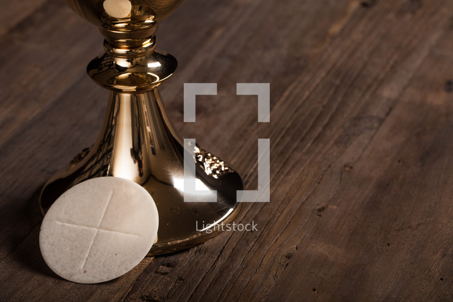 A single communion wafer leaning against a golden goblet.