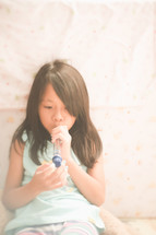 a girl playing a toy flute