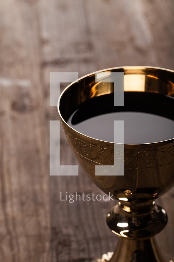 A golden communion goblet full of wine on a wooden surface.