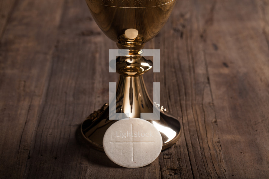 A golden wine goblet and a communion wafer on a wooden surface.