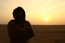 man standing in a desert with a scarf over his head