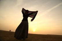 woman dancing with a scarf in the desert