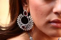 A woman wearing a very large earring with gemstones and pearls.