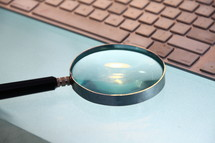 A magnifying glass held over a computer keyboard.