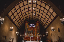A soaring roof and an ornate pipe organ in a church.