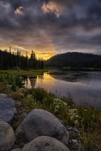 a mountain lake under a cloudy sky at sunset