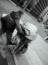 homeless man pushing a shopping cart