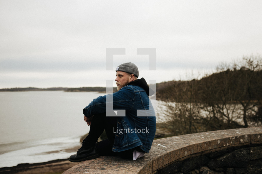 a man sitting on a wall looking out at a lake under a gloomy sky