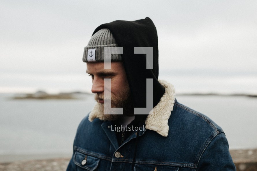 a man in a beanie standing by a shore