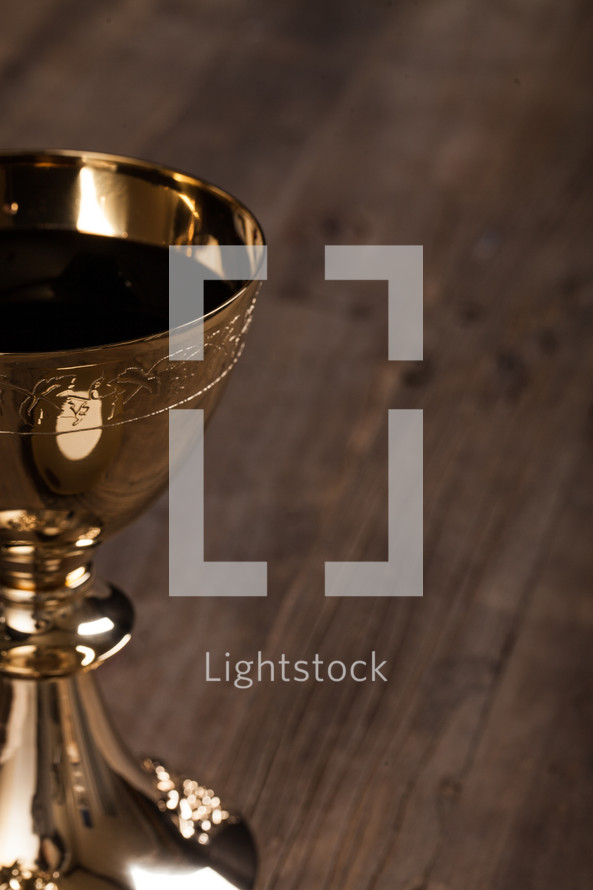 A golden communion goblet filled with wine.