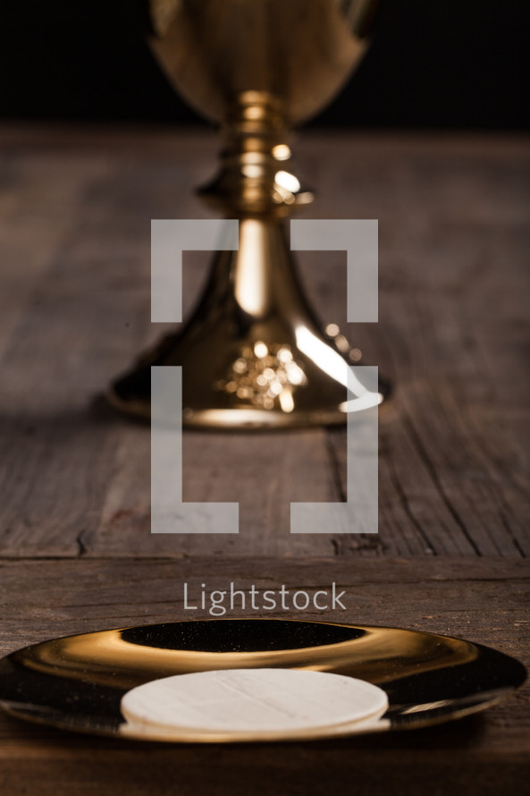 A communion wafer and golden communion goblet on a rustic wooden table.