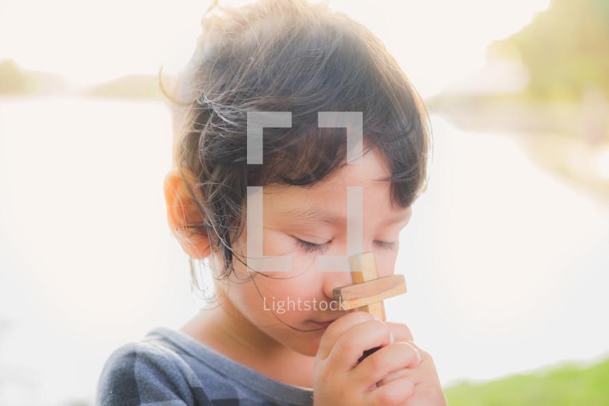 a toddler girl holding a wooden cross