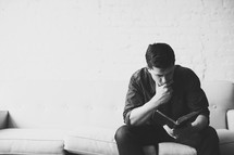 Man sitting on a sofa reading the Bible.
