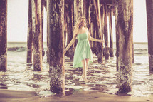 A woman walking in the water under a pier at a beach.