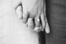 Engaged couple's intertwined hands.