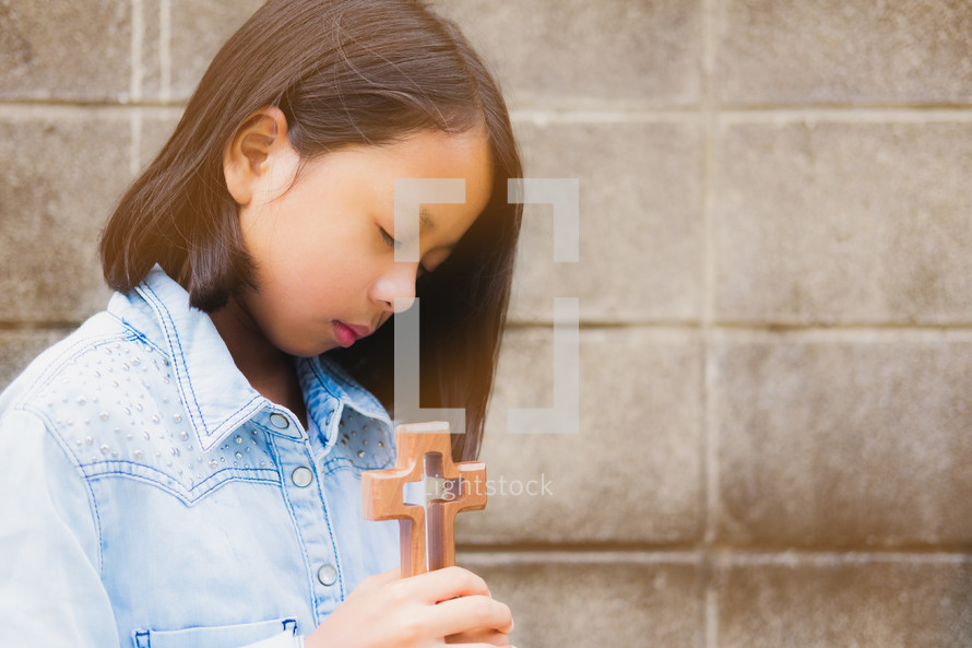 girl holding a wooden cross
