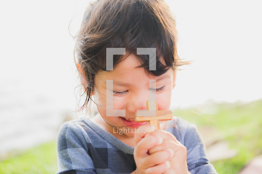 a toddler girl holding a wooden cross