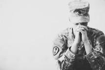 Female soldier in uniform praying.