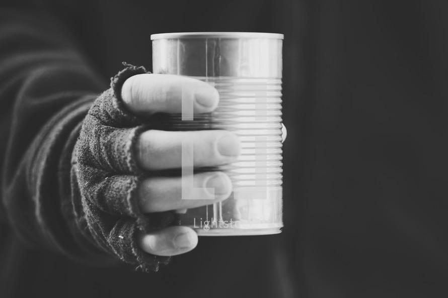 beggar holding a tin can