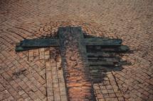 wood cross on brick road