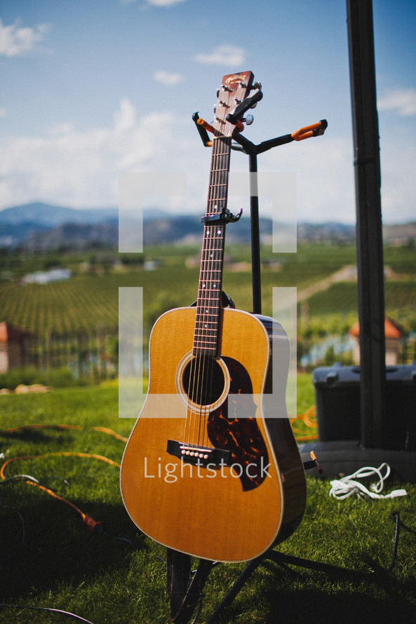 Accoustical guitar on stand in grassy yard with blue sky and mountains on the horizon.